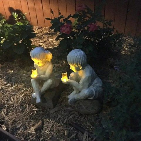 Creatively Statues Of 2 Kids Holding Fireflies.